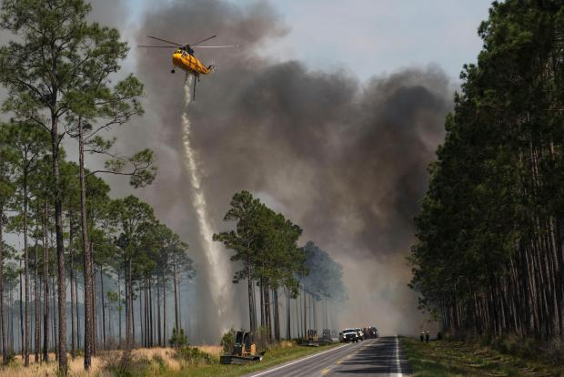A helicopter makes a water drop next to the road in Okefenokee National Wildlife Refuge on the West Mims Fire. Photo via InciWeb.